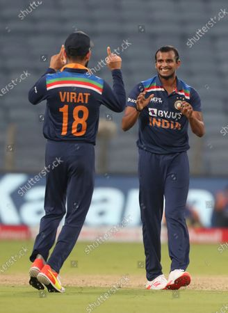 India's T Natrajan, right, celebrates with captain Virat Kohli after the dismissal of England's Ben Stokes during the third One Day International cricket match between India and England at Maharashtra Cricket Association Stadium in Pune, India