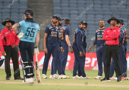Indian players await third umpire's decision for the wicket of England's Ben Stokes, second left, during the third One Day International cricket match between India and England at Maharashtra Cricket Association Stadium in Pune, India