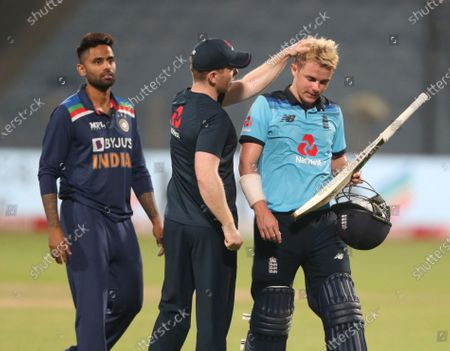 Stock Photo of England's Eoin Morgan, center, pats teammate Sam Curran as he walks off the field after their loss in the third One Day International cricket match between India and England at Maharashtra Cricket Association Stadium in Pune, India, . India Won the series 2-1