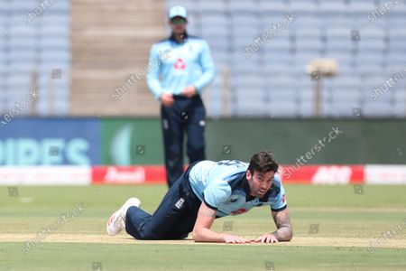 England's Reece Topley falls in an attempt to field the ball during the third One Day International cricket match between India and England at Maharashtra Cricket Association Stadium in Pune, India
