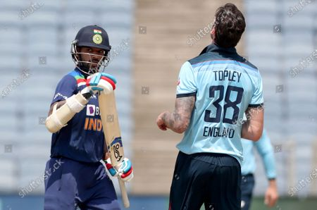 Stock Photo of England's Reece Topley, right, reacts as India's Shikhar Dhawan, left, runs between the wickets to score during the third One Day International cricket match between India and England at Maharashtra Cricket Association Stadium in Pune, India