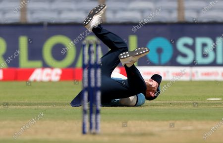 England's Ben Stokes falls in an attempt to field the ball during the third One Day International cricket match between India and England at Maharashtra Cricket Association Stadium in Pune, India