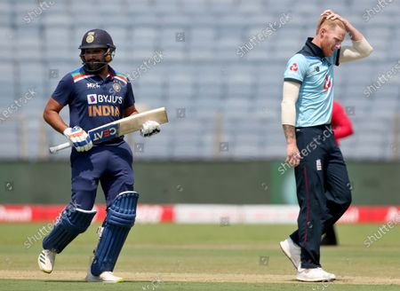 England's Ben Stokes, right, reacts after bowling a delivery to India's Rohit Sharma, left, during the third One Day International cricket match between India and England at Maharashtra Cricket Association Stadium in Pune, India