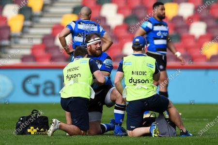 Henry Thomas of Bath Rugby is treated for an injury