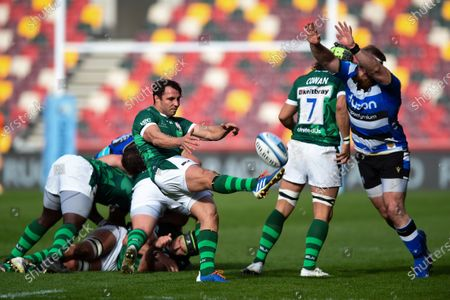 Stock Picture of Nick Phipps of London Irish box-kicks the ball as Henry Thomas of Bath Rugby looks to charge him down