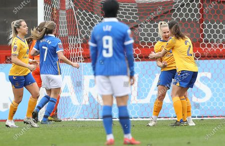 Izzy Christiansen (2nd R) of Everton celebrates after she scores a penalty to make it 1-0