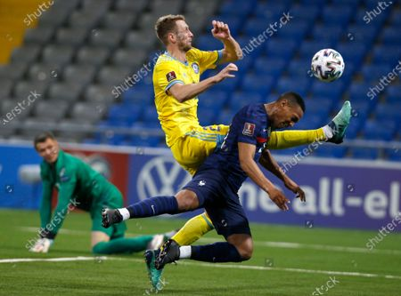 Kazakhstan's Sergey Maliy, centre, and France's Anthony Martial challenge for the ball during the World Cup 2022 group D qualifying soccer match between Kazakhstan and France at the Astana Arena stadium in Nur-Sultan, Kazakhstan