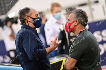 Former Formula One driver Gerhard Berger, of Austria, left, speaks with former Formula 1 driver Jean Alesi, of France, at the starting grid prior to the start of the Bahrain Formula One Grand Prix at the Bahrain International Circuit in Sakhir, Bahrain
