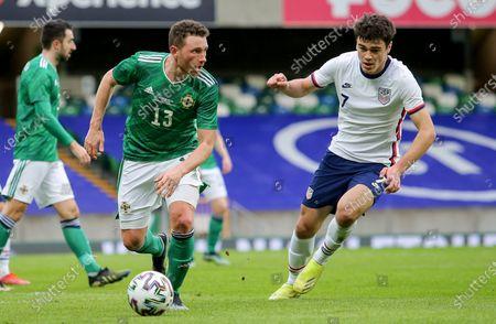 Stock Photo of Northern Ireland vs USA. Northern Ireland's Corry Evans and USA's Gio Retna