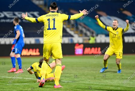 Ludwig Augustinsson (bottom) of Sweden celebrates with team-mates Zlatan Ibrahimovic (L) and Viktor Claesson (R) after scoring the 1-0 lead during the FIFA World Cup 2022 qualifying soccer match between Kosovo and Sweden in Pristina, Kosovo, 28 March 2021.