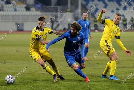 Sweden's Mikael Lustig, left, and Sweden's Viktor Claesson, right, challenge Kosovo's Arber Zeneli during the World Cup 2022 group B qualifying soccer match between Kosovo and Sweden at the Fadil Vokrri stadium in Pristina, Kosovo