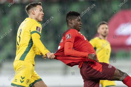 Lithuania's Vytas Gaspuitis (L) pulls the jersey of Switzerland's Breel Embolo (R) during the FIFA World Cup Qatar 2022 qualifying Group C soccer match between Switzerland and Lithuania at the Kybunpark stadium in St. Gallen, Switzerland, 28 March 2021.