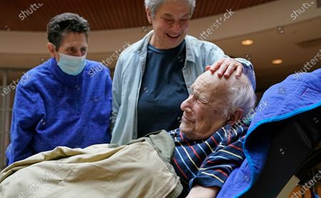 Stock Picture of Melvin Goldstein, 90, smiles as his daughter Barbara Goldstein places her hand on his head during their first in-person, indoor family visit inside the Hebrew Home at Riverdale, in the Bronx borough of New York. The younger Goldstein's spouse Judy Disco, left, stands by watching the pair's reunion. Due to earlier COVID-19 protocols, only outdoor visits through the windows had been allowed