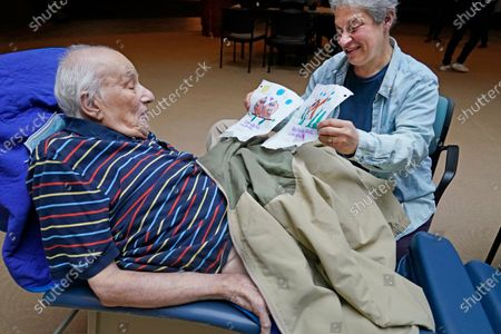 Stock Photo of Melvin Goldstein, 90, glances at pictures of birds, left, and a fish, his 13-year-old granddaughter drew for him as a gift as his daughter Barbara Goldstein shares them with his during a family visit inside the Hebrew Home at Riverdale, in New York. Due to loosening restrictions to prevent the spread of the coronavirus, it was the first weekend in over a year families had been allowed to visit with residents inside the facility at close-range. Previously, families had to remain outdoors at a distance and visit through the nursing home's windows