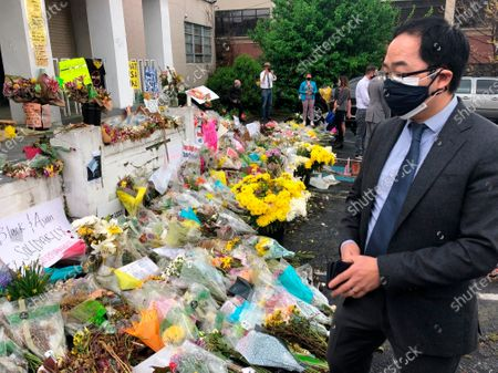 New Jersey Rep. Andy Kim looks over flowers and messages at a memorial for the victims of the March 16 shootings in front of Gold Spa, one of the shooting sites on in Atlanta