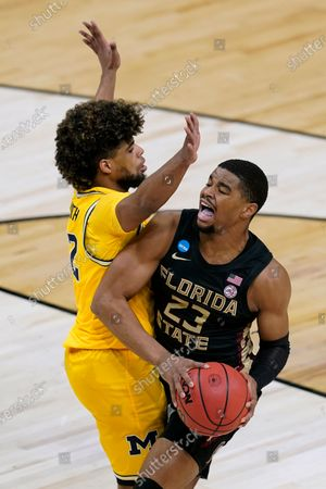 Florida State guard M.J. Walker (23) drives around Michigan guard Mike Smith, left, during the first half of a Sweet 16 game in the NCAA men's college basketball tournament at Bankers Life Fieldhouse, in Indianapolis