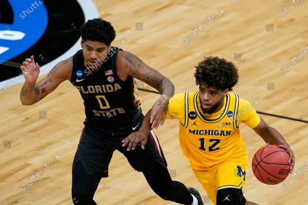 Michigan guard Mike Smith (12) drives up court ahead of Florida State guard RayQuan Evans (0) during the second half of a Sweet 16 game in the NCAA men's college basketball tournament at Bankers Life Fieldhouse, in Indianapolis
