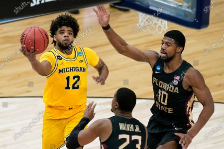 Michigan guard Mike Smith (12) drives to the basket over Florida State guard M.J. Walker (23) and forward Malik Osborne (10) during the second half of a Sweet 16 game in the NCAA men's college basketball tournament at Bankers Life Fieldhouse, in Indianapolis