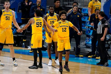 Michigan guard Mike Smith (12) celebrates with teammates during the second half of a Sweet 16 game against Florida State in the NCAA men's college basketball tournament at Bankers Life Fieldhouse, in Indianapolis