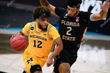 Michigan guard Mike Smith (12) drives up court ahead of Florida State guard Anthony Polite (2) during the first half of a Sweet 16 game in the NCAA men's college basketball tournament at Bankers Life Fieldhouse, in Indianapolis
