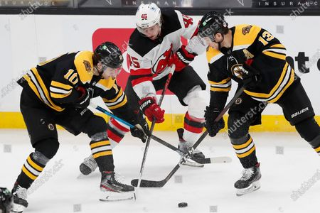 New Jersey Devils' Sami Vatanen (45) battles Boston Bruins' Anders Bjork (10) and Charlie Coyle (13) for the puck during the first period of an NHL hockey game, in Boston