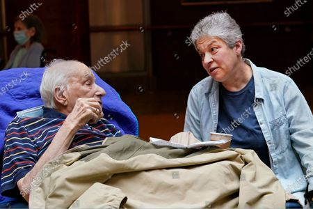 Barbara Goldstein talks to her 90 year-old father Melvin Goldstein as he eats cookies during an indoor family visit at the Hebrew Home at Riverdale, in New York. It was the first weekend in over a year the Bronx nursing home allowed in-person, indoor family visits for residents following the loosening of protocols designed to prevent the spread of coronavirus. Previously visits had been confined to distanced, outdoor visits through the facility's windows