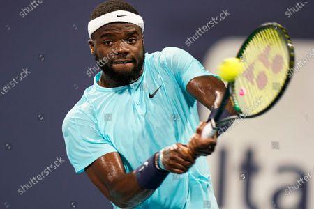 Frances Tiafoe returns a shot from Dusan Lajovic, of Serbia, during the Miami Open tennis tournament, in Miami Gardens, Fla