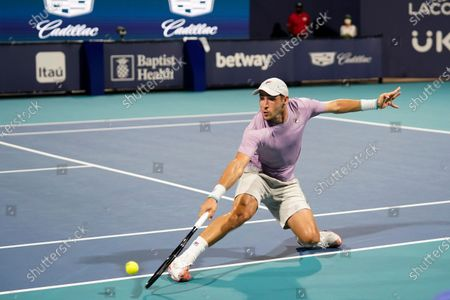 Dusan Lajovic, of Serbia, returns a shot from Frances Tiafoe during the Miami Open tennis tournament, in Miami Gardens, Fla