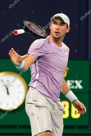 Dusan Lajovic, of Serbia, tosses his tennis racquet after losing a point to Frances Tiafoe during the Miami Open tennis tournament, in Miami Gardens, Fla