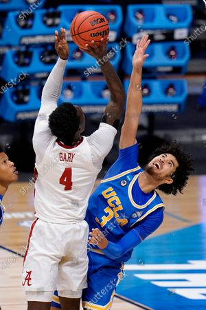 Stock Image of Alabama forward Juwan Gary (4) shoots on UCLA guard Johnny Juzang (3) in the first half of a Sweet 16 game in the NCAA men's college basketball tournament at Hinkle Fieldhouse in Indianapolis