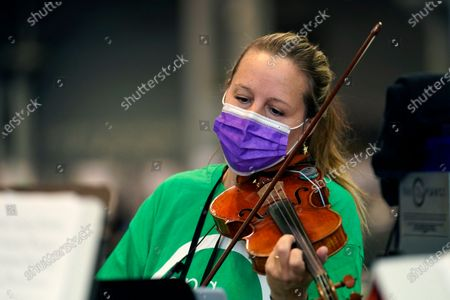 """Violinist Victoria Paterson plays with a string quartet as people are inoculated at the Jacob K. Javits Convention Center, which has been converted into a mass vaccination site, in New York. Paterson, who toured with Barbra Streisand and has played in Broadway pit orchestras, found herself playing for tips when the pandemic closed New York cultural sites last March. But she was prepared after playing for a difference audience__hospitals, retirement home and community centers. She founded the nonprofit 'Music & Medicine' """"because there was no Broadway, no churches, no synagogues, and no concert halls"""" during the pandemic. Paterson and the nonprofit 'Sing for Hope' are helping fellow musicians get back on their feet, paying them to perform daily midday concerts at the convention center, which has vaccinated over a quarter of a million people have been vaccinated since mid-January"""