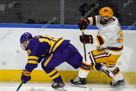 Minnesota State forward Reggie Lutz, left, becomes entangled with Minnesota forward Ben Meyers in the second period of an NCAA College Hockey Regional Final, in Loveland, Colo