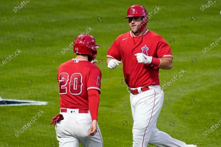 Los Angeles Angels' Jared Walsh, left, and Mike Trout congratulate each other after they scored on a ball hit by Albert Pujols during the third inning of a spring training exhibition baseball game, in Anaheim, Calif. Los Angeles Dodgers' Corey Seager was charged with a fielding error on the play
