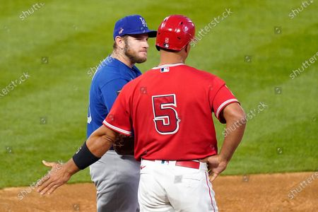 Los Angeles Dodgers first baseman Max Muncy, left, and Los Angeles Angels' Albert Pujols chat as they stand on first during the third inning of a spring training exhibition baseball game, in Anaheim, Calif