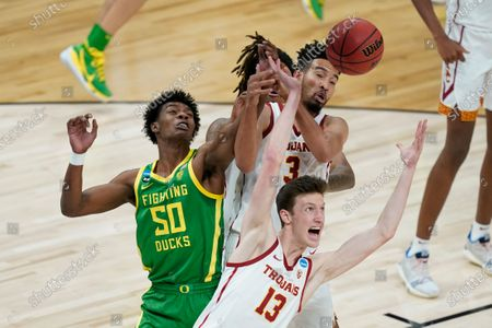 Southern California guard Drew Peterson (13) battles for a rebound with Oregon forward Eric Williams Jr. (50) during the first half of a Sweet 16 game in the NCAA men's college basketball tournament at Bankers Life Fieldhouse, in Indianapolis