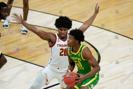 Oregon forward Eric Williams Jr. (50) drives past Southern California guard Ethan Anderson (20) during the first half of a Sweet 16 game in the NCAA men's college basketball tournament at Bankers Life Fieldhouse, in Indianapolis