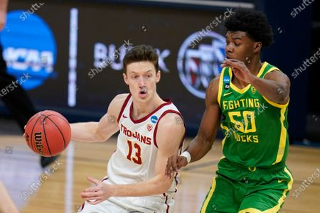 Southern California guard Drew Peterson (13) drives past Oregon forward Eric Williams Jr. (50) during the first half of a Sweet 16 game in the NCAA men's college basketball tournament at Bankers Life Fieldhouse, in Indianapolis
