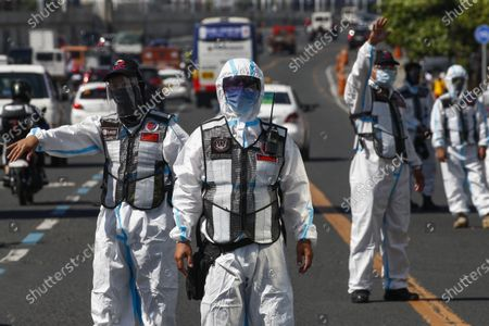 Government transportation inspectors wearing protective suits against COVID-19 wait for public transport vehicles to be checked for social distancing protocols along Commonwealth Avenue in Quezon City, Metro Manila, Philippines 29 March 2021. President Rodrigo Duterte ordered the Enhanced Community Quarantine (ECQ), the most restrictive type of lockdown in the country's four-level quarantine measures, during the Lenten season. Police checkpoints have been tightened at various border points in Metro Manila and nearby provinces from 29 March to 04 April.