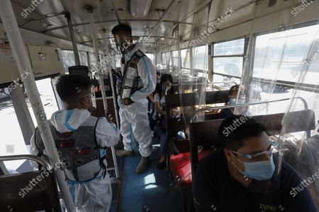 Government transportation inspectors wearing protective suits against COVID-19 check a passenger bus for social distancing protocols along Commonwealth Avenue in Quezon City, Metro Manila, Philippines 29 March 2021. President Rodrigo Duterte ordered the Enhanced Community Quarantine (ECQ), the most restrictive type of lockdown in the country's four-level quarantine measures, during the Lenten season. Police checkpoints have been tightened at various border points in Metro Manila and nearby provinces from 29 March to 04 April.