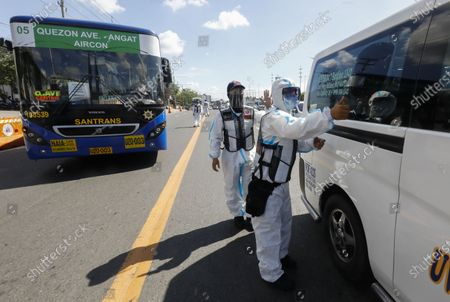 Government transportation inspectors wearing protective suits against COVID-19 gesture to a minibus after checking passemgers' social distancing protocols along Commonwealth Avenue in Quezon City, Metro Manila, Philippines 29 March 2021. President Rodrigo Duterte ordered the Enhanced Community Quarantine (ECQ), the most restrictive type of lockdown in the country's four-level quarantine measures, during the Lenten season. Police checkpoints have been tightened at various border points in Metro Manila and nearby provinces from 29 March to 04 April.