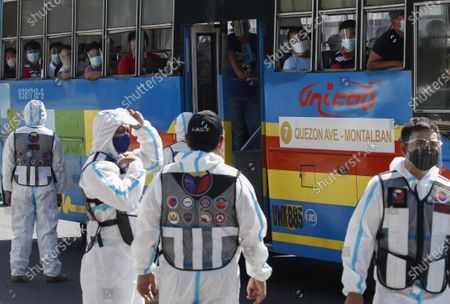 Bus passengers look out at government transportation inspectors wearing protective suits against COVID-19 along Commonwealth Avenue in Quezon City, Metro Manila, Philippines 29 March 2021. President Rodrigo Duterte ordered the Enhanced Community Quarantine (ECQ), the most restrictive type of lockdown in the country's four-level quarantine measures, during the Lenten season. Police checkpoints have been tightened at various border points in Metro Manila and nearby provinces from 29 March to 04 April.