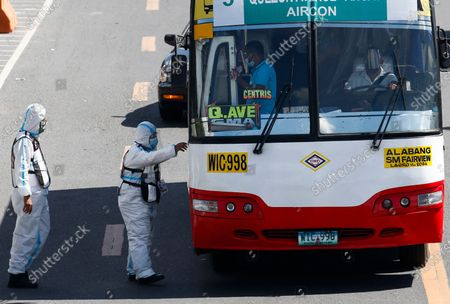 Government transportation inspectors wearing protective suits against COVID-19 board a bus to check passengers' social distancing protocols along Commonwealth Avenue in Quezon City, Metro Manila, Philippines 29 March 2021. President Rodrigo Duterte ordered the Enhanced Community Quarantine (ECQ), the most restrictive type of lockdown in the country's four-level quarantine measures, during the Lenten season. Police checkpoints have been tightened at various border points in Metro Manila and nearby provinces from 29 March to 04 April.