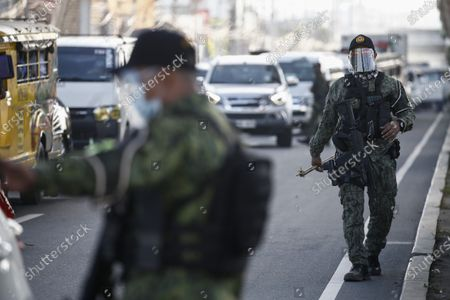 Police officers keep watch at a checkpoint set up to prevent non-essential travels by citizens at the boundary of Rizal province and Marikina City, Metro Manila, Philippines 29 March 2021. President Rodrigo Duterte ordered the Enhanced Community Quarantine (ECQ), the most restrictive type of lockdown in the country's four-level quarantine measures, during the Lenten season. Police checkpoints have been tightened at various border points in Metro Manila and nearby provinces from 29 March to 04 April.
