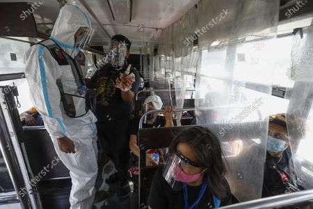 A government transportation inspector (L) wearing a protective suit against COVID-19 talks to a bus fare collector (2nd L) during a check on bus passengers' social distancing protocols along Commonwealth Avenue in Quezon City, Metro Manila, Philippines 29 March 2021. President Rodrigo Duterte ordered the Enhanced Community Quarantine (ECQ), the most restrictive type of lockdown in the country's four-level quarantine measures, during the Lenten season. Police checkpoints have been tightened at various border points in Metro Manila and nearby provinces from 29 March to 04 April.