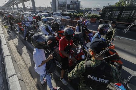 Motorcycle riders queue at a police checkpoint set up to prevent non-essential travels by citizens at the boundary of Rizal province and Marikina City, Metro Manila, Philippines 29 March 2021. President Rodrigo Duterte ordered the Enhanced Community Quarantine (ECQ), the most restrictive type of lockdown in the country's four-level quarantine measures, during the Lenten season. Police checkpoints have been tightened at various border points in Metro Manila and nearby provinces from 29 March to 04 April.