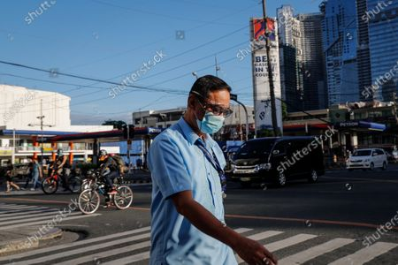 A man crosses a street in the business district of Makati, south of Manila, Philippines, 29 March 2021. President Rodrigo Duterte ordered the Enhanced Community Quarantine (ECQ), the most restrictive type of lockdown in the country's four-level quarantine measures, during the Lenten season. Police checkpoints have been tightened at various border points in Metro Manila and nearby provinces from 29 March to 04 April.