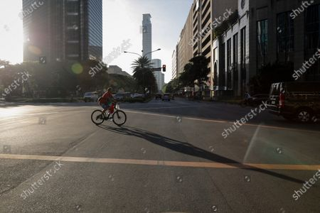 A man rides a bicycle to work in the business district of Makati, south of Manila, Philippines, 29 March 2021. President Rodrigo Duterte ordered the Enhanced Community Quarantine (ECQ), the most restrictive type of lockdown in the country's four-level quarantine measures, during the Lenten season. Police checkpoints have been tightened at various border points in Metro Manila and nearby provinces from 29 March to 04 April.