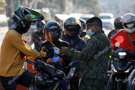 Motorcycle riders present their identification cards to police personnel at a checkpoint in Pasay City, south of Manila, Philippines, 29 March 2021. President Rodrigo Duterte ordered the Enhanced Community Quarantine (ECQ), the most restrictive type of lockdown in the country's four-level quarantine measures, during the Lenten season. Police checkpoints have been tightened at various border points in Metro Manila and nearby provinces from 29 March to 04 April.