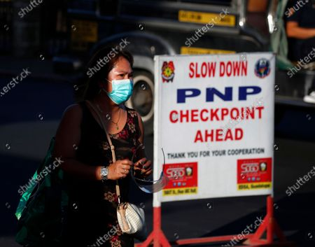 A Filipino motorist walks past a checkpoint at the border between Las Pinas city, and Cavite province, Philippines, 29 March 2021. President Rodrigo Duterte ordered Enhanced Community Quarantine (ECQ), the most restrictive type of lockdown in the country's four-level quarantine measures, during the Lenten season. Police checkpoints have been tightened at various border points in Metro Manila and nearby provinces from 29 March to 04 April.