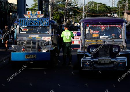 A Filipino traffic enforcer checks passengers of a jeepney at a checkpoint at the border between Las Pinas city, and Cavite province, Philippines, 29 March 2021. President Rodrigo Duterte ordered Enhanced Community Quarantine (ECQ), the most restrictive type of lockdown in the country's four-level quarantine measures, during the Lenten season. Police checkpoints have been tightened at various border points in Metro Manila and nearby provinces from 29 March to 04 April.
